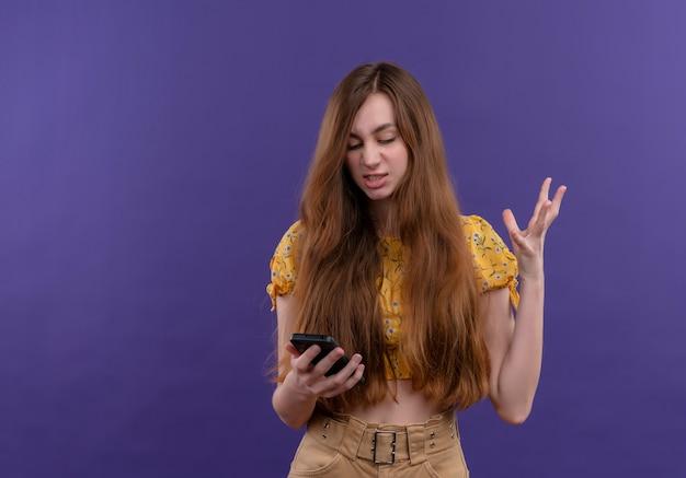 Раздраженная молодая девушка держит мобильный телефон и поднимает руку на изолированном фиолетовом пространстве с копией пространства