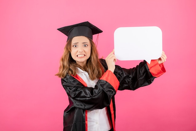 Annoyed young girl holding white idea board and wearing graduation gown on pink wall.