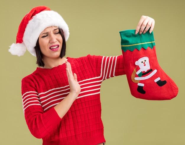 Раздраженная молодая девушка в шляпе санта-клауса держит рождественский чулок, глядя на него, делая отказный жест, изолированный на оливково-зеленой стене