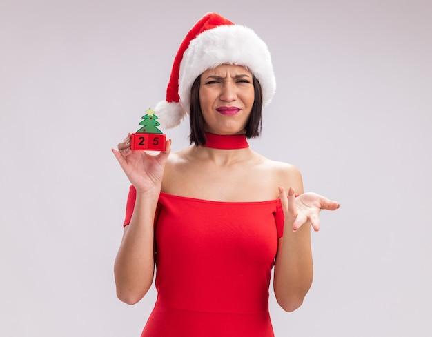 흰색 배경에 고립 된 빈 손을 보여주는 카메라를보고 날짜와 크리스마스 트리 장난감을 들고 산타 모자를 쓰고 짜증이 어린 소녀