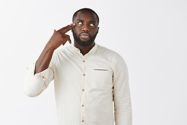 Annoyed young guy posing against the white wall
