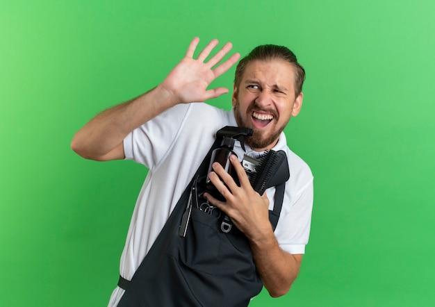 Раздраженный молодой красивый парикмахер в униформе держит расчески, баллончик с распылителем, машинки для стрижки волос и смотрит в сторону и не делает никаких жестов, изолированных на зеленом фоне с копией пространства