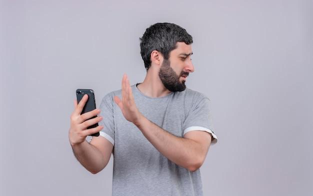 イライラする若いハンサムな白人男性が携帯電話を持って横を見て、コピースペースで白に孤立して身振りで示すことはありません
