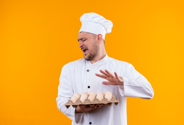 Annoyed young handsome cook in chef uniform holding carton of eggs and gesturing no isolated on orange wall