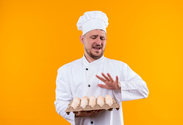 Annoyed young handsome cook in chef uniform holding carton of eggs gesturing no isolated on orange wall