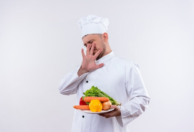 Infastidito giovane bel cuoco in uniforme da chef tenendo piatto con verdure e gesticolando no sul muro bianco isolato