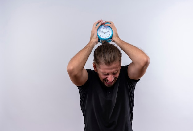 Раздраженный молодой красавец в черной рубашке поло держит будильник, который собирается бросить и сломать его, стоя на белом фоне