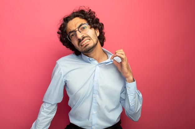 분홍색 벽에 고립 된 셔츠의 칼라를 잡는 전면을보고 안경을 쓰고 짜증이 젊은 잘 생긴 남자