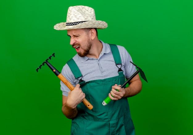 Раздраженный молодой красивый славянский садовник в униформе и шляпе держит грабли и грабли, глядя на грабли