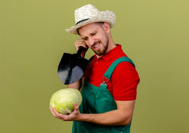 キャベツを見て、コピースペースのあるオリーブグリーンの壁に隔離されたその上にスペードを保持している縦断ビューで立っている制服と帽子のイライラした若いハンサムなスラブの庭師