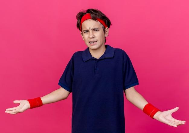 Раздраженный молодой красивый спортивный мальчик в головной повязке и браслетах с зубными скобами, глядя вперед, показывая пустые руки, изолированные на малиновой стене