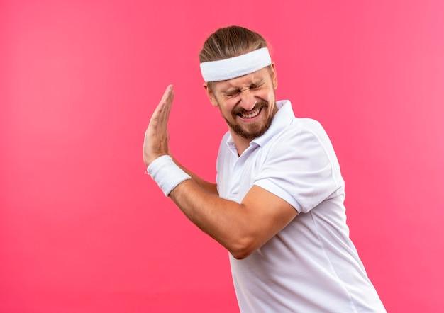 Раздраженный молодой красивый спортивный мужчина с повязкой на голову и браслетами, не делающий жестов сбоку с закрытыми глазами, изолирован на розовой стене с копией пространства
