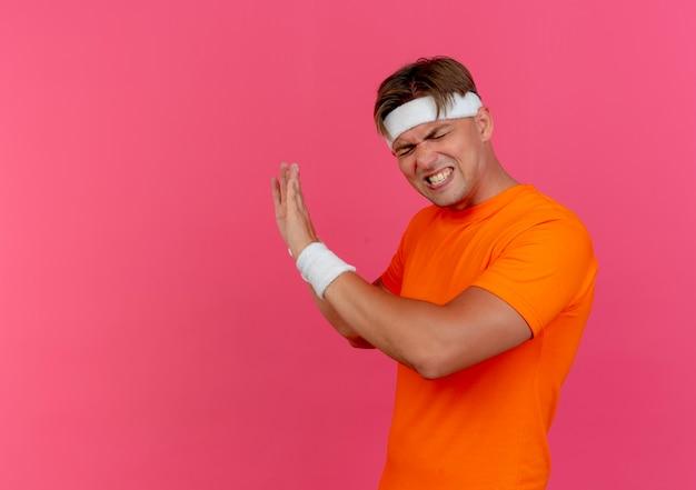 Раздраженный молодой красивый спортивный мужчина с повязкой на голову и браслетами, стоящий в профиле, жестикулирующий с закрытыми глазами, изолированными на розовом с копией пространства
