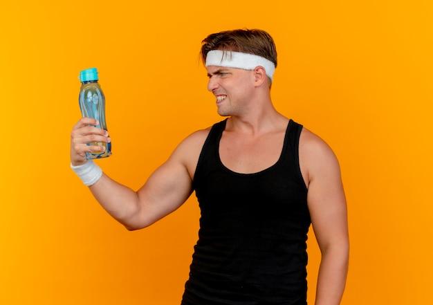 Infastidito giovane uomo sportivo bello indossando la fascia e braccialetti che tengono e che esaminano la bottiglia di acqua isolata sull'arancio