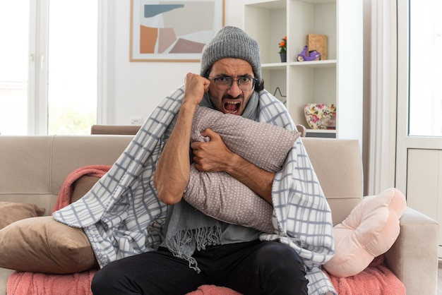 Раздраженный молодой больной человек в оптических очках, завернутый в плед, с шарфом на шее, в зимней шапке, обнимает подушку и держит кулак, сидя на диване в гостиной