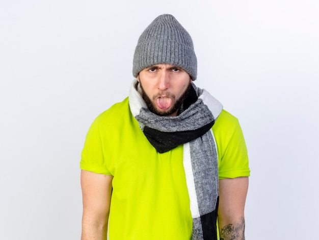 Annoyed young ill man wearing winter hat and scarf stucks out tongue isolated on white wall