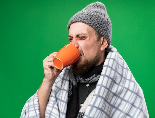 Annoyed young ill slavic man with scarf around neck wrapped in plaid wearing winter hat drinks from cup isolated on green wall with copy space
