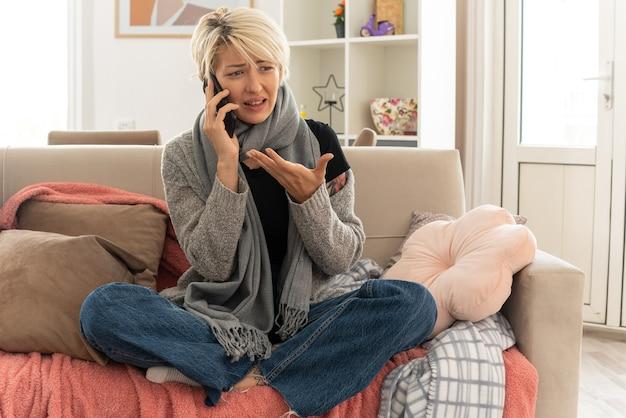 リビングルームのソファに座って電話で話している彼女の首の周りにスカーフを持つイライラした若い病気のスラブ女性