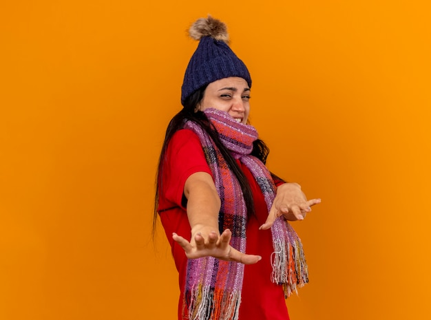 Annoyed young ill woman wearing winter hat and scarf standing in profile view stretching out hands towards front looking at front gesturing no isolated on orange wall