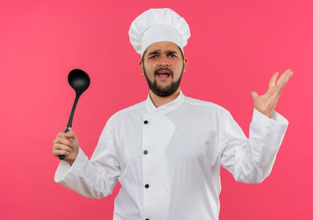 Giovane cuoco maschio infastidito in uniforme da chef che tiene in mano un mestolo e mostra la mano vuota isolata sulla parete rosa