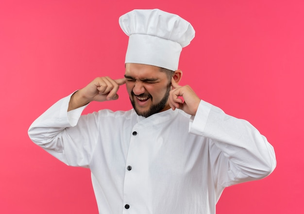 Annoyed young male cook in chef uniform putting fingers in ears with closed eyes isolated on pink wall