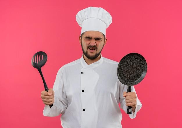 ピンクの壁にフライパンと穴の開いたスプーンを保持しているシェフの制服を着たイライラした若い男性料理人