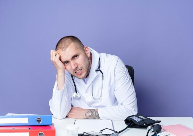 Infastidito giovane medico maschio indossa abito medico e stetoscopio seduto alla scrivania con strumenti di lavoro mettendo la mano sulla testa isolata sulla porpora