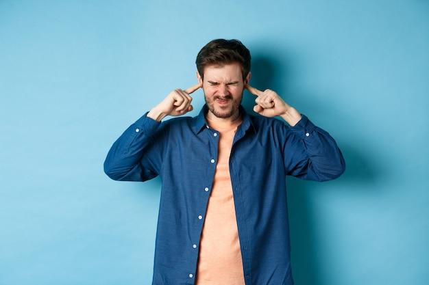 성가신 청년 블록 소리, 손가락으로 귀를 닫고 찡그린 소리로 시끄러운 음악에 방해 받고 파란색 배경에 서 있습니다.