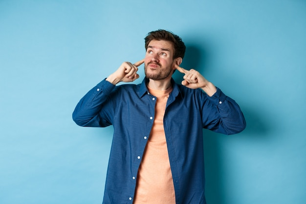 Annoyed young man block sound, shut ears with fingers and grimacing, disturbed by loud neighbours, looking up irritated, standing on blue background.