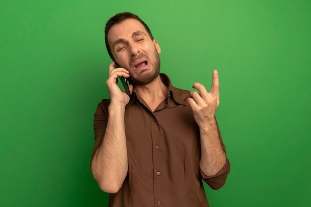 녹색 벽에 고립 된 닫힌 된 눈으로 가리키는 전화로 얘기 짜증이 젊은 남자