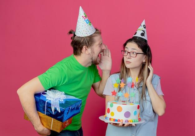 Il giovane infastidito che indossa il cappello del partito tiene le scatole regalo che guardano e gridano alla ragazza che indossa il cappello del partito e che tiene la torta di compleanno isolata sulla parete rosa