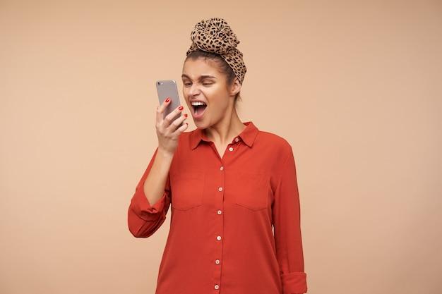 Infastidita giovane signora dai capelli castani con la fascia alzando la mano con il telefono cellulare alla bocca mentre urla di malcontento nel microtelefono, in posa sul muro beige