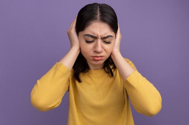 Infastidita giovane bella ragazza caucasica che copre le orecchie con le mani con gli occhi chiusi isolati sul muro viola