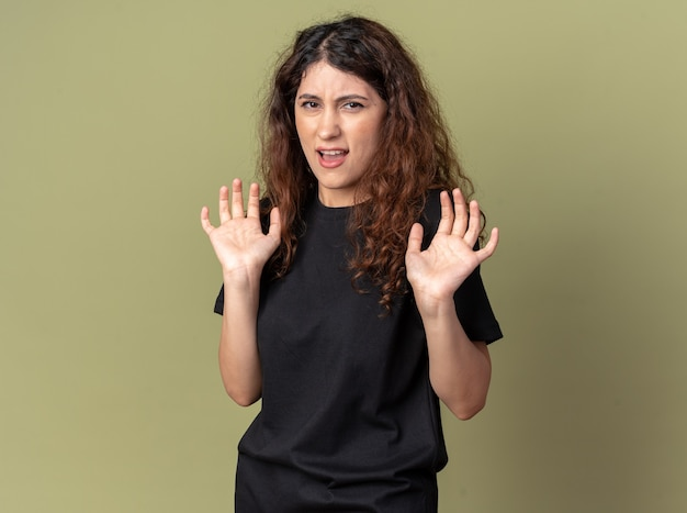 Annoyed young pretty caucasian girl  doing refusal gesture isolated on olive green wall with copy space