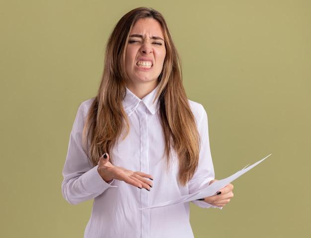 Una giovane ragazza caucasica infastidita tiene e indica fogli di carta bianca isolati su una parete verde oliva con spazio per le copie