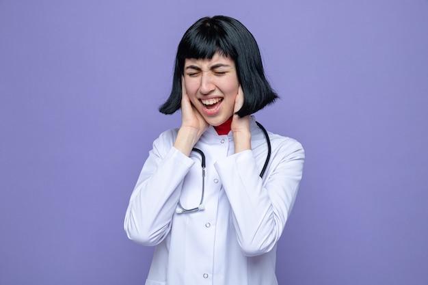 手で彼女の耳を覆う聴診器で医者の制服を着たイライラする若いかなり白人の女の子