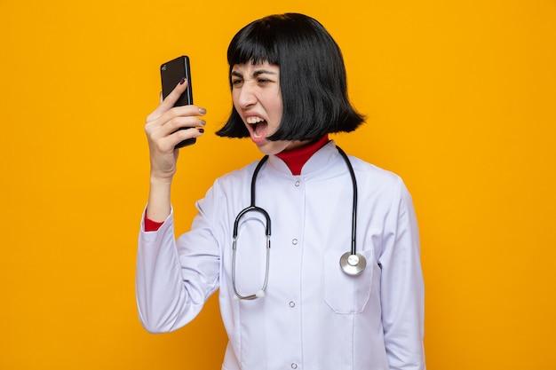 전화로 누군가에게 고함을 지르는 청진기를 들고 의사 제복을 입은 화난 젊은 백인 소녀