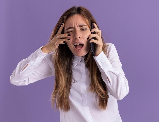 Раздраженная молодая симпатичная кавказская девушка разговаривает по телефону и кладет руку на лицо, изолированное на фиолетовой стене с копией пространства