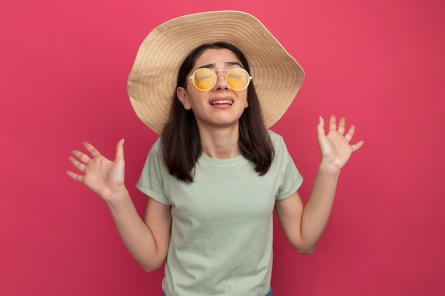 目を閉じて空の手を示すビーチ帽子とサングラスを身に着けているイライラする若いかなり白人の女の子