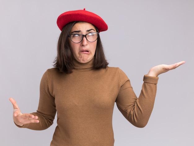 ベレー帽の帽子と光学メガネで目を転がし、コピースペースで白い壁に隔離された手を開いて保持しているイライラする若いかなり白人の女の子