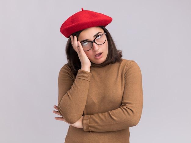 Раздраженная молодая симпатичная кавказская девушка в берете и в оптических очках закатывает глаза и кладет руку на лицо