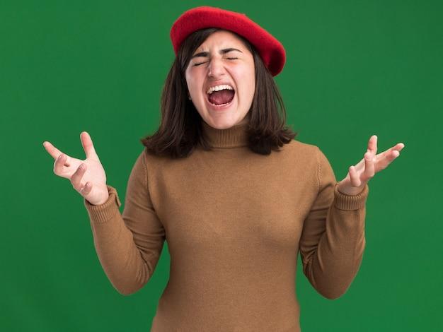 コピースペースと緑の壁に分離された手を開いてベレー帽の帽子をかぶったイライラする若いかなり白人の女の子