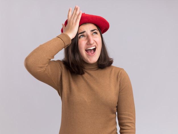 La giovane ragazza piuttosto caucasica infastidita con il cappello del berretto mette la mano sulla fronte e guarda in su