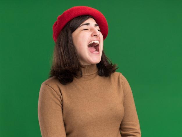 La giovane ragazza abbastanza caucasica infastidita con il cappello del berretto urla sul verde