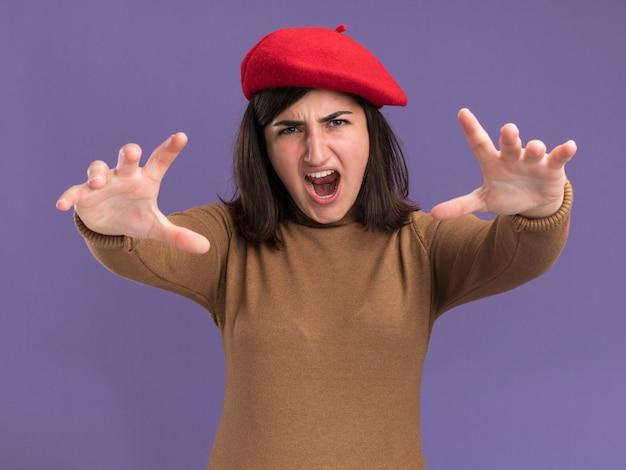 コピースペースで紫色の壁に分離された手を伸ばすベレー帽の帽子を持つイライラする若いかなり白人の女の子