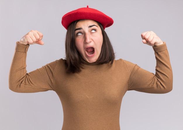 La giovane ragazza piuttosto caucasica infastidita con il berretto tende i bicipiti e guarda in alto