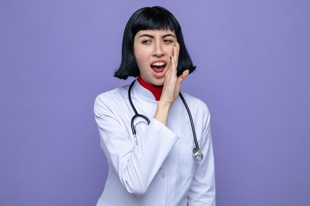 의사 제복을 입은 젊고 예쁜 백인 여성이 청진기를 입에 가까이 대고 옆을 바라보고 있다