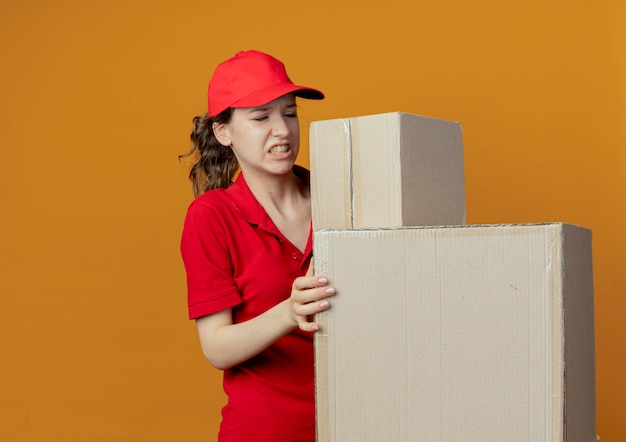 Annoyed young pretty delivery girl in red uniform and cap holding and looking at carton boxes isolated on orange background with copy space