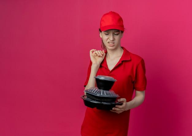 赤い制服と帽子を身に着けて、コピースペースで深紅色の背景に分離された食品容器を保持し、見てイライラする若いかわいい配達の女の子