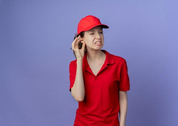 Раздраженная молодая симпатичная доставщица в красной форме и кепке смотрит в сторону, положив руку на ухо, изолированную на фиолетовом фоне с копией пространства